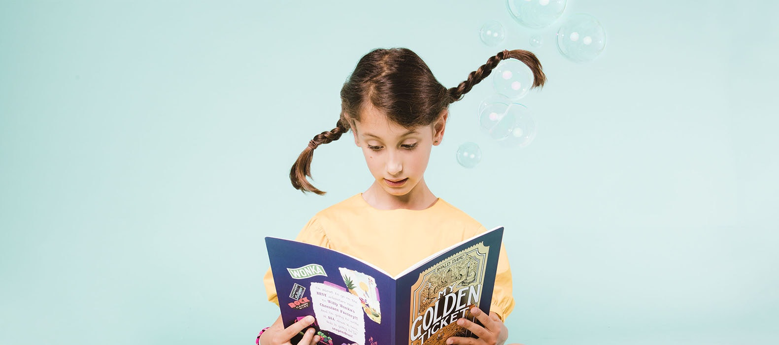 girl reading a my golden ticket book with bubbles around her
